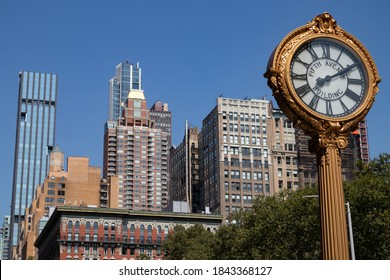 New York, New York / USA - September 8 2020: Gold Fifth Avenue Building Street Clock in Midtown Manhattan with Skyscrapers in New York City