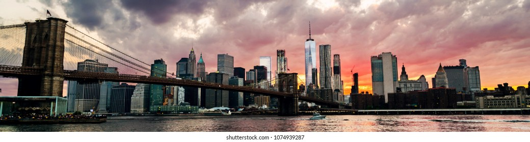 New York, USA. View of Manhattan bridge and Manhattan in New York, USA at sunset. Colorful cloudy sky with illuminated skyscrapers. Sun setting behind the skyscrapers