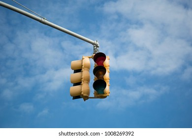 New York yellow traffic light with red light against blue sky background