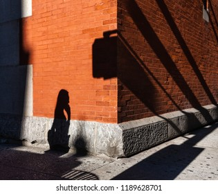 New York and New Yorkers. Light and shadows Manhattan street scene. Americans on the streets of NYC. People go to work early morning against brick wall background