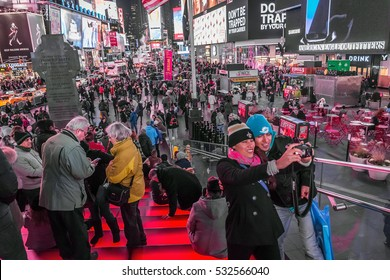 NEW YORK-DECEMBER 7: A couple among the huge crowd takes a selfie on December 7 2016 in Times Square, New York City.