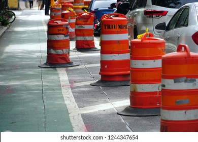 New York/Manhattan/USA - 7 October 2018: Road Work signs on the Street. Long line of orange traffic barrier barrels to detour traffic around construction zone.