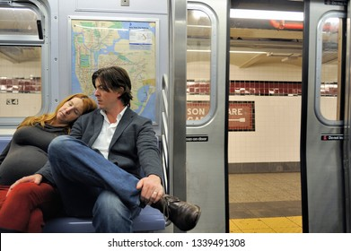 NEW YORK,USA-NOVEMBER 11,2012: Loving couple sitting in the subway, while pregnant wife is sleeping