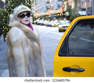 NEW YORK,USA-NOVEMBER 14,2012: Wel dressed lady in fur coat entering a cab in Manhattan