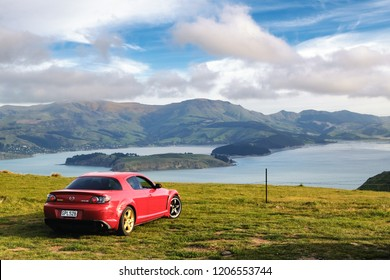 NEW ZEALAND, CHRISTCHURCH, PORT HILLS - NOVEMBER 2015: A red Mazda RX-8 car parked on top of Port Hills overlooking a crater lake.