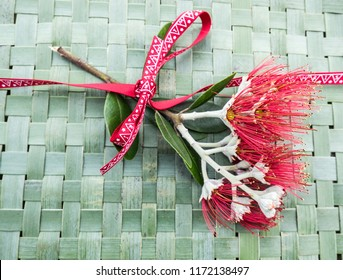 New Zealand Christmas Tree or Pohutukawa flower on woven green flax kete background with ribbon - kiwiana NZ xmas theme