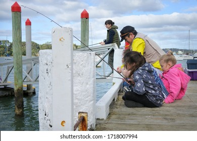 New Zealand family fishing together from a boat jetty in Taipa Bay-Mangonui in Northland North Island of  New Zealand. Real people. Copy space.
