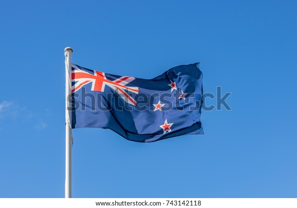 New Zealand Flag Flying High In Blue Sky On Anzac Day