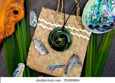 New Zealand - Maori themed objects - greenstone jade pendant with carved wooden mere on woven kite flax bag with abalone - paua shells on grey stone background