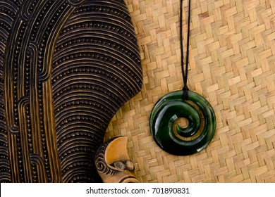 New Zealand - Maori themed objects - carved wooden mere and greenstone pendant on woven kite flax background