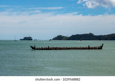 New Zealand Maori Waka (long canoe) Crossing bay of islands during Waitangi Day, New Zealand Navy Ship In Distance for 21 gun salute.
