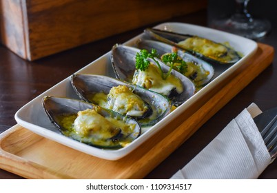 New Zealand Mussels Gratin with cheese on white Ceramic plate