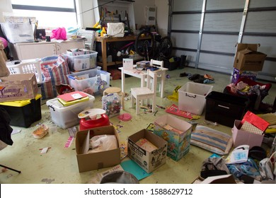 New Zealand - October 2 2019: Garage full of stuff, exercise equipment, clothes, junk. Looks like moving, decluttering, unpacking. Plastic tubs and boxes filled, empty. Typical scene spring cleaning