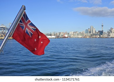 The New Zealand Red Ensign wave against Auckland city skyline, New Zealand.