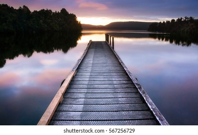 New Zealand - Simple wooden jetty leads into still empty lake to forests and hills beyond in beautiful light reflected in the water.
