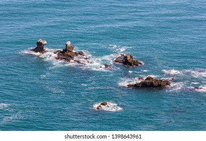 New Zealand. Small rocks in the ocean near west coast of the South Island is washed by the waves of the Tasman Sea