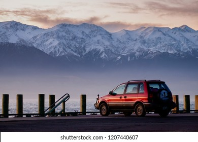 NEW ZEALAND, SOUTH ISLAND, KAIKOURA - JULY 2016: A red 1995 Mitsubishi RVR 4WD vehicle parks at the coast line of Kaikoura overlooking majestic snow mountain in early morning.