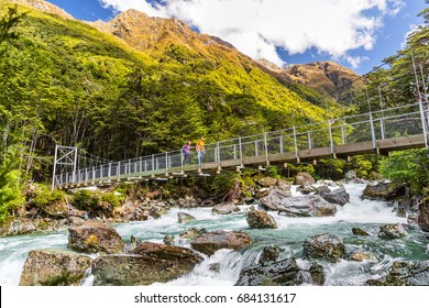 New Zealand tramping people crossing river bridge. Hikers couple backpackers walking hiking together with backpacks on Routeburn Track trail path.