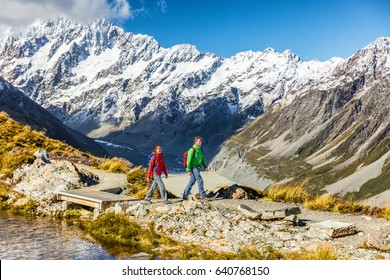 New zealand travel hikers hiking in Mt Cook trail to Mueller Hut. Tramping lifestyle couple tourists walking on alpine route in alps with snow capped mountains in background.