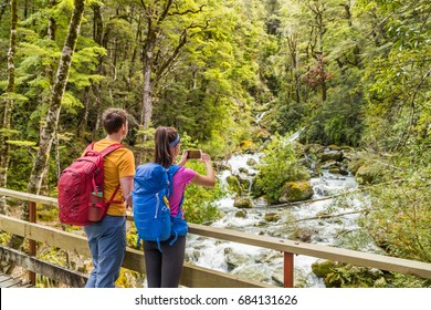 New zealand travel tourists taking phone picture on tramping hike in forest with backpacks. Woman holding smartphone taking photos of river on Routeburn track hiking trail on South Island.