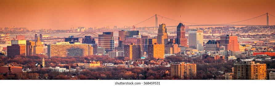 Newark New Jersey skyline viewed from Eagle Rock reservation under an orange sunset.