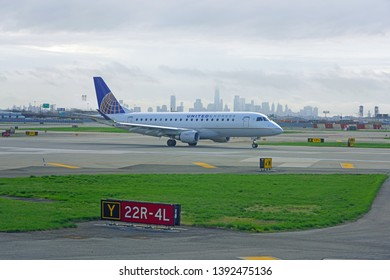 NEWARK, NJ -21 APR 2019- View of a plane from United Airlines (UA) at Newark Liberty International Airport (EWR) in New Jersey with the New York City Manhattan skyline in the background .
