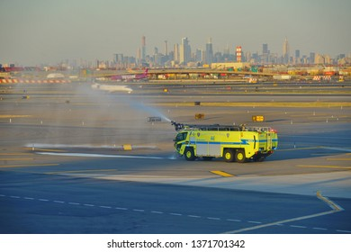 NEWARK, NJ -3 APR 2019- View of yellow airport firetrucks spraying water on the tarmac at Newark Liberty International Airport (EWR) with the New York City skyline in the background.