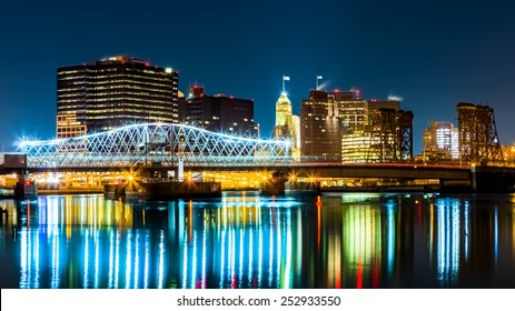 Newark, NJ cityscape by night, viewed from Riverbank park. Jackson street bridge, illuminated, spans the Passaic River