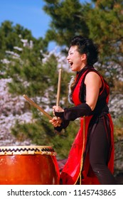 Newark, NJ, USA April 21, 2007 A young woman enthusiastically demonstrates the ancient art of Japanese Taiko drumming at a spring festival in Newark, New Jersey