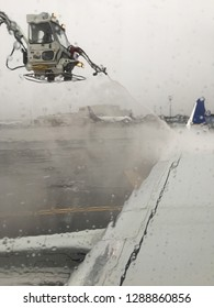 Newark, NJ, USA March 13, 2018 Workers deice the wing of a commercial airliner on a cold, stormy day in Newark, New Jersey