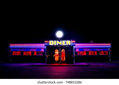NEWARK, UK - NOVEMBER 2, 2017 A traditional American Diner at night with a large sign and colourful luminous, fluorescent and neon lighting that glows in the dark.