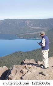 NEWBERRY CRATER, OREGON - OCT 22, 2018 - Tourist using mobile phone on Paulina Peak, with Newberry National Volcanic Monument, Oregon