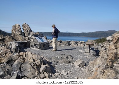 NEWBERRY CRATER, OREGON - OCT 22, 2018 - Tourist reading  information display in Big Obsidian Flow, Newberry National Volcanic Monument, Oregon