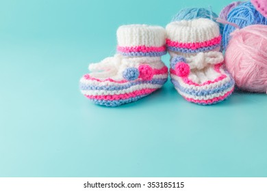 Newborn announcement concept. Knitted booties on aquamarine background with yarn clew