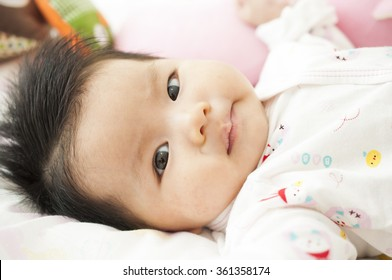Newborn asian baby girl  play and smile on bed