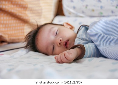 Newborn Asian baby sleeping on bed. Maternity family childhood innocence care concept. Selective focus at little hand
