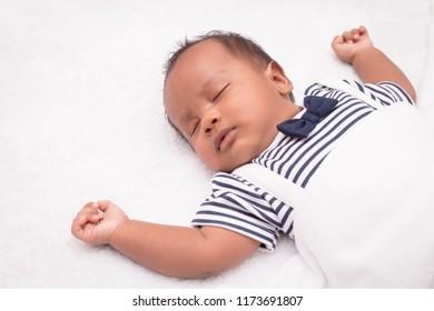 newborn asian boy baby sleeping on white furry cloth