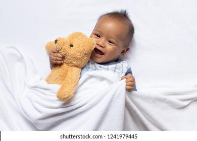 newborn asian boy baby sleeping with bear on white furry cloth