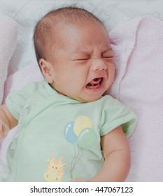 newborn Asian unhappy baby boy wear green dress lying and crying on pink and white blanket : people and health care concept