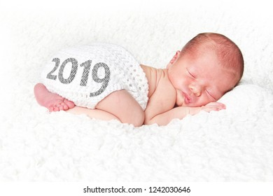 Newborn baby asleep on a white blanket with 2019 on his knitted diaper cover. Happy New Year baby.