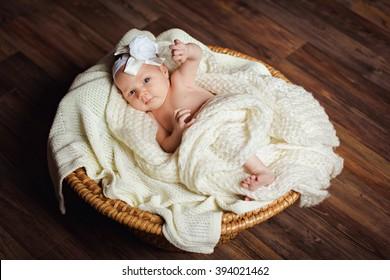 A newborn baby in the basket. A newborn little girl.