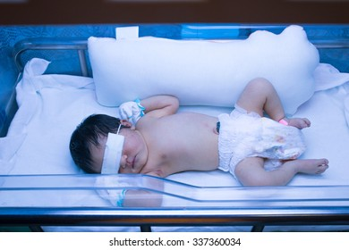 newborn baby being treatment by ultraviolet light in incubator.