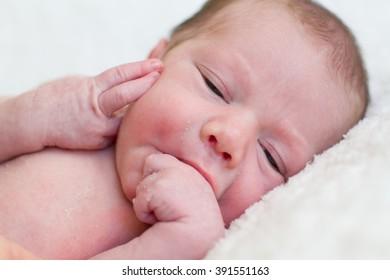 Newborn baby biting his hand , lyingd on a white blanket.