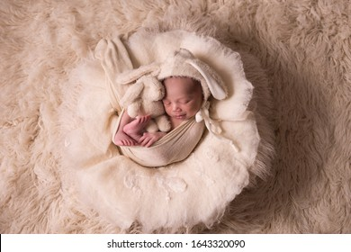 Newborn baby boy, 10 days old, sleeping and wrapped in a blanket.  He is wearing a tiny beanie with bunny ears, and is also holding a stuffed bunny in his arms.