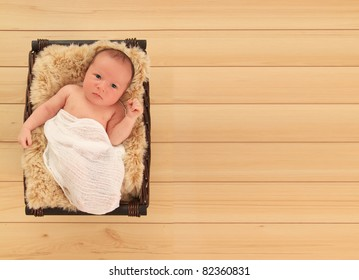 Newborn baby boy awake in a basket.