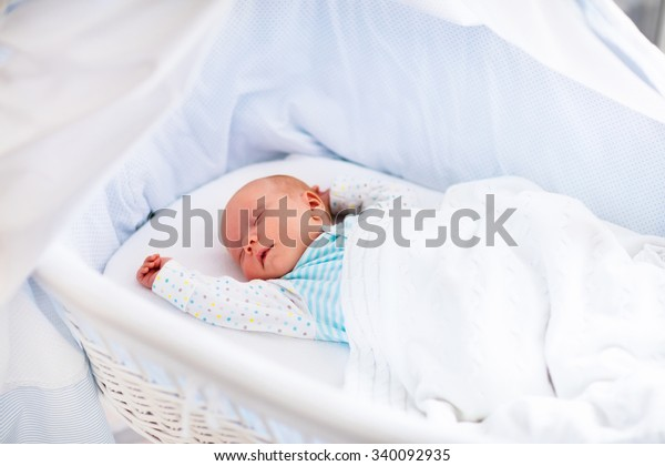 Newborn baby boy in bed. New born child sleeping under a white knitted blanket. Children sleep. Bedding for kids. Infant napping in bed. Healthy little kid shortly after birth. Cable knit textile.