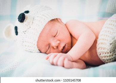 The newborn baby boy dressed in bear-like clothes