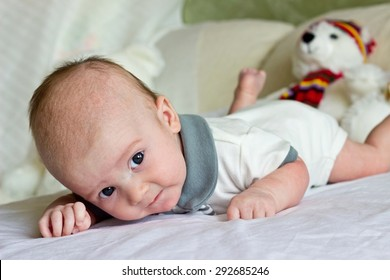 Newborn baby boy lying on bed with toys and looking at camera