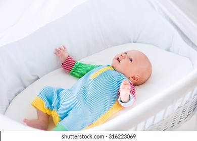 Newborn baby boy playing in bed on a sunny morning. New born child relaxing in bassinet. Children sleep. Bedding and clothing for kids. Infant napping in bed. Healthy little kid shortly after birth.