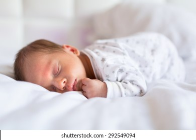 Newborn baby boy sleeping in bed
